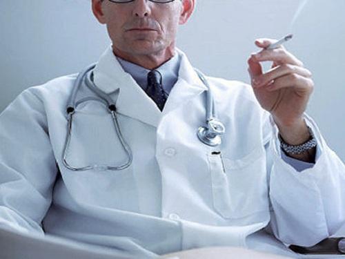 Doctor in lab coat smoking a cigarette   Original Filename: 88300580.jpg